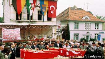 Dozens of people attend a funeral where red Turkish flags are draped over the coffins