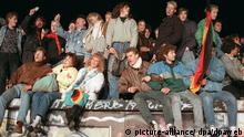 Singend und schunkelnd freuen sich junge Menschen auf der Berliner Mauer über die Grenzöffnung (Archivbild vom 10.11.1989). Die Hoffnung für viele DDR-Bürger hieß im Sommer 1989 Ungarn. Im Trabi, Wartburg oder per Zug machten sie sich unauffällig auf den Weg in die Freiheit - immer in Angst, auf der Flucht in den Westen zu zeitig entdeckt zu werden. Am 9. November 1989 fiel dann die Mauer. Jetzt jährt sich das historische Ereignis zum 15. Mal. Foto: Peter Kneffel dpa (zum dpa-Korr.-Bericht Massenfluchten, Montagsdemos und Freudentaumel - 15 Jahre Mauerfall vom 12.08.2004)
