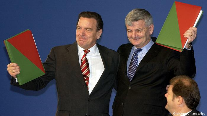 An archived photo shows former Chancellor Gerhard Schröder with his arm around Greens leader Joschka Fischer. Both hold a red and green folder containing their parties' newly signed coalition agreement.
