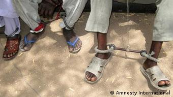 Prisoners feet chained on both legs. Copyright: Amnesty International
