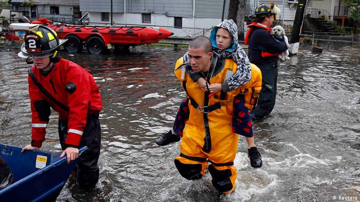 A rescue worker carries a boy on his back as emergency personnel rescue residents from flood waters brought on by Hurricane Sandy