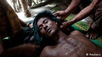 Mohammad Nur, 28, faints while hiding with his wife Samuda Khatun and son Shahid Noor in a house in Teknaf October 30, 2012. (Photo: REUTERS/Andrew Biraj)