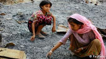 Members of a Muslim Rohingya family gather at the ruins of their home(Photo: Reuters)