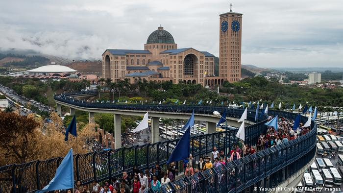 Pilgrims cross the pedestrian bridge that connects the old and new basilicas of Our Lady of Aparecida during Brazil patron saint's day in Aparecida, 170 km east of Sao Paulo, Brazil, on October 12, 2012. Accounts claim that the 39-cm-high teracotta statuette of Our Lady of Aparecida was caught in their net by three fishermen in 1717, and became Brazil's national patroness in 1930. The Basilica, the world largest Marian will receive 146,000 pilgrims this year. AFP PHOTO/Yasuyoshi CHIBA (Photo credit should read YASUYOSHI CHIBA/AFP/GettyImages)