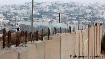An ultra-Orthodox Jewish man (L) overlooks the Palestian town of Bethlehem as he stands at the end of a raffiti-painted protective wall in the Gilo neighborhood in the southern part of Jerusalem that is due to be taken down in the coming days, Jerusalem, Israel on 14 August 2010. The wall was was put up during the 'al-Aqsa Intifada,' the second Palestinian uprising that began in 2000, and was meant to protect Gilo residents from bullets fired from nearby Bethlehem and Beit Jala, some of which did hit Israeli homes in that era. Israel now thinks the walls are not needed for protection. EPA/JIM HOLLANDER