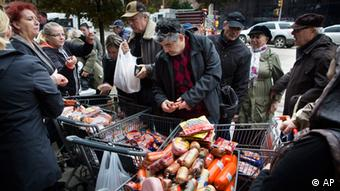 A customer browses food piled into shopping carts on Brighton Beach Avenue, Wednesday, Oct. 31, 2012, in the Brooklyn borough of New York. People in the coastal corridor battered by superstorm Sandy took the first cautious steps Wednesday to reclaim routines upended by the disaster, even as rescuers combed neighborhoods strewn with debris and scarred by floods and fire. (Foto: John Minchillo/AP/dapd)