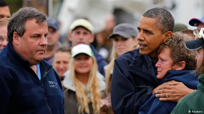 U.S. President Barack Obama hugs North Point Marina owner Donna Vanzant as he tours damage done by Hurricane Sandy in Brigantine, New Jersey, October 31, 2012. At left is New Jersey Governor Chris Christie. Putting aside partisan differences, Obama and Christie toured storm-stricken parts of New Jersey together on Wednesday, taking in scenes of flooded roads and burning homes in the aftermath of superstorm Sandy. REUTERS/Larry Downing (UNITED STATES - Tags: POLITICS DISASTER)
