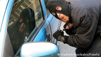 A masked man stages an auto theft