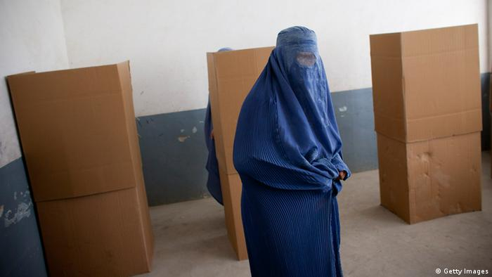 An Afghan woman votes at a polling station for the parliamentary elections. Photo by Majid Saeedi/Getty Images)