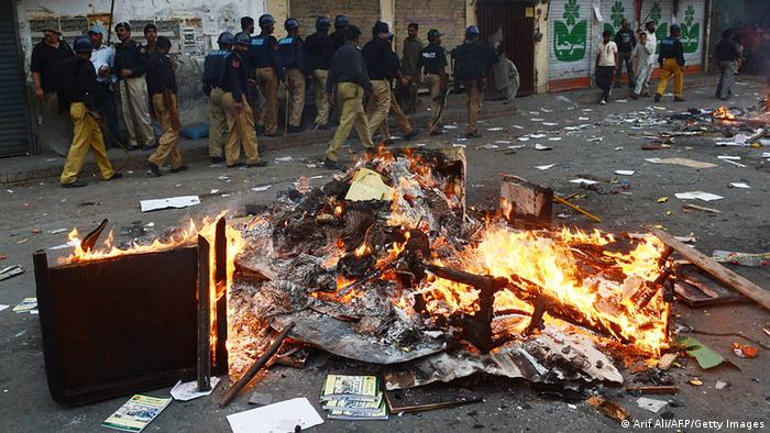 Pakistani police walk past burning furniture that was set to fire by an angry mob near a school following a protest over blasphemy allegations (Photo: Arif Ali/AFP/Getty Images)