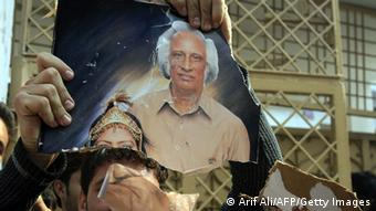 Pakistani demonstrators tear the photo of the school owner during a protest (Photo: Arif Ali/AFP/Getty Images)