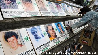 A woman puts a picture amid others during a demonstration against the false positives, massacres and forced disappearences by Colombian authorities on March 6, 2009, in Medellin, Antioquia Department, Colombia. AFP PHOTO/Raul ARBOLEDA (Photo credit should read RAUL ARBOLEDA/AFP/Getty Images)