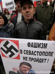 A middle-aged man wearing a black jacket and black baseball cap looks forlorn as he holds a white poster bearing a nazi swastika and a picture of a member of the nationalist Svoboda party. (Photo: Alexei Pavlishak)