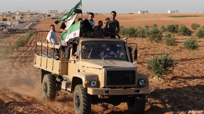 Free Syrian Army fighters with opposition flags ride a truck which they say was captured from the Syrian army loyal to President Bashar al-Assad, in Saraqeb near Idlib REUTERS/Shaam News Network/Handout (