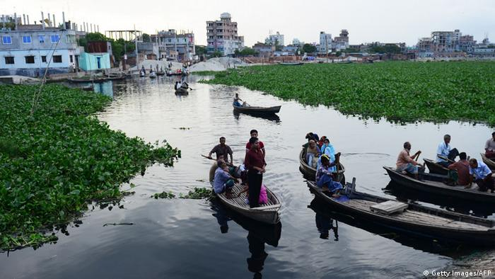 Bangladeshi commuters use boats to commute on the Buriganga river in Dhaka on September 18, 2012. Large amounts of water hyacinths have hampered the movement of boats on the river for the thousands of commuters that use them. AFP PHOTO/Munir uz ZAMAN (Photo credit should read MUNIR UZ ZAMAN/AFP/GettyImages)