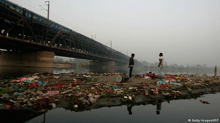 Two Indians stand on an island filled with trash, prior to performing as part of an art installation by artist Asim Waqif, on the Yamuna river in New Delhi on November 20, 2011.