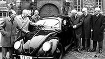 Black and white photo taken in 1938 of a Volkswagen Beetle, surrounded by the group of men who designed and engineered the classic model