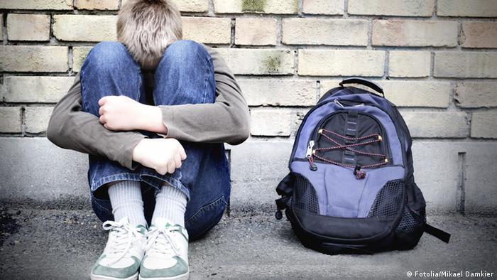 Ein Junge sitzt auf dem Boden an eine Wand gelehnt.