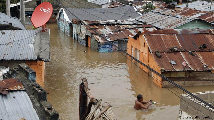 Ein Mann kämpft sich durch eine überschwemmte Straße (Foto: EFE)