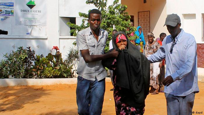 People assist a girl wounded in a suicide blast at popular restaurant in Mogadishu, Saturday, Nov. 3, 2012. A police official says a security guard died while fending off suicide bombers who were trying to storm into a popular Mogadishu restaurant. (Foto:Farah Abdi Warsameh/AP/dapd)