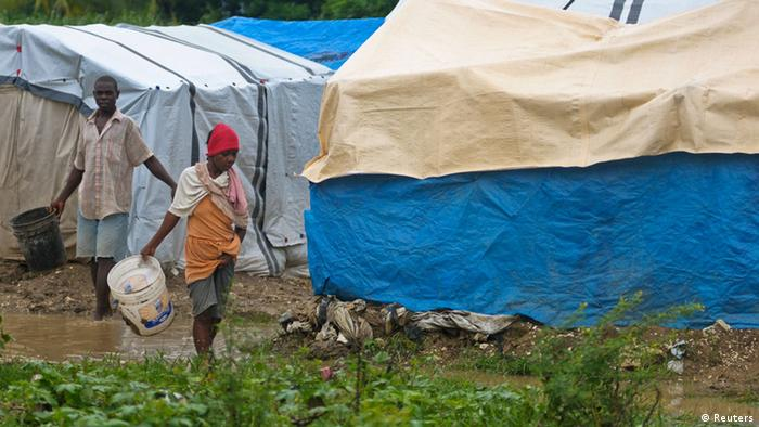 Haitians walk through mud after rains from Hurricane Sandy flooded their tent encampment in Port-au-Prince (Photo: Swoan Parker)
