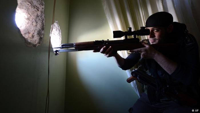 A Syrian rebel fighter takes aim at government forces, from a flat in a rebel controlled building on the front line in Aleppo's northern Izaa quarter, on November 3, 2012. Syrian rebels said they had launched a major assault on a northern airbase used to deploy regime air power, on the eve of a crucial meeting to decide the future of the opposition. AFP PHOTO/PHILIPPE DESMAZES (Photo credit should read PHILIPPE DESMAZES/AFP/Getty Images)