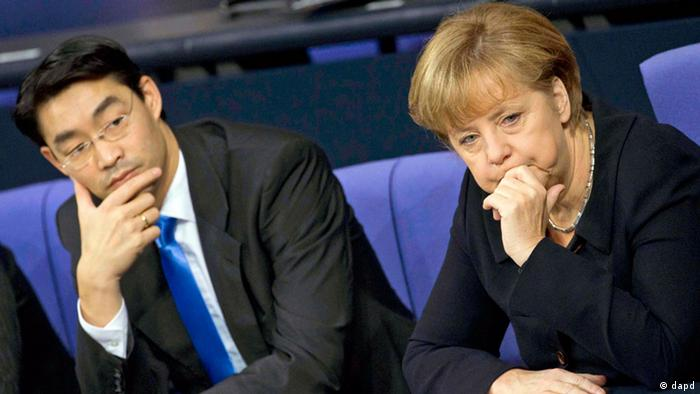 German Chancellor Angela Merkel from the Christian Democrats, right, and Vice Chancellor Philipp Roesler from the Free Democrats listen to the debate at the parliament Bundestag in Berlin, (Photo:Markus Schreiber, File/AP/dapd).