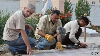 Гастарбайтеры в России кладут плитку на тротуаре