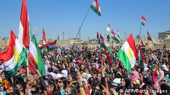 Syrian Kurds wave the Kurdish flag as they rally against the Syrian regime AFP/GettyImages