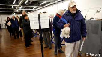 A man carries his dog as he waits in line to turn in his ballot during the U.S. presidential election, at a polling station set up for those affected by Hurricane Sandy, in an art gallery at John Jay College, in New York, November 6, 2012. REUTERS/Chip East (UNITED STATES - Tags: POLITICS USA PRESIDENTIAL ELECTION ELECTIONS ANIMALS)
