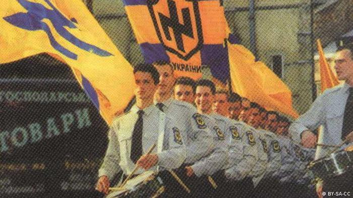 Young Ukrainians wearing identical blue uniforms and carrying blue and yellow flags march through the street in tandem while drumming nationalist songs. (Photo: Wikipedia commons)