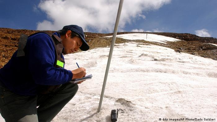 With a GPS to locate a point in the Bolivian Andes mountain Range, Bolivian glaciologist, or ice specialist, Edson Ramirez, measures the thickness of Bolivian tropical glacier Chacaltaya, near Bolivian capital La Paz, Dec. 6, 2004. Chacaltaya, a frozen storehouse of such water, will be gone in seven to eight years, said Ramirez, an evidence of the global warming. In the foreground, the snowy cap of the mountain is seen split in two, a phenomena seen for the first time ever, according to Ramirez.(ddp images/AP Photo/Dado Galdieri)