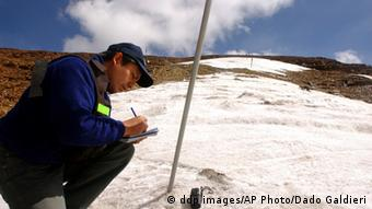 A researcher measures the depth of a glacier's ice