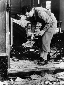 A worker clearing broken glass of a Jewish shop following the anti-Jewish riots of Kristallnacht in Berlin. (Photo by Hulton Archive/Getty Images)