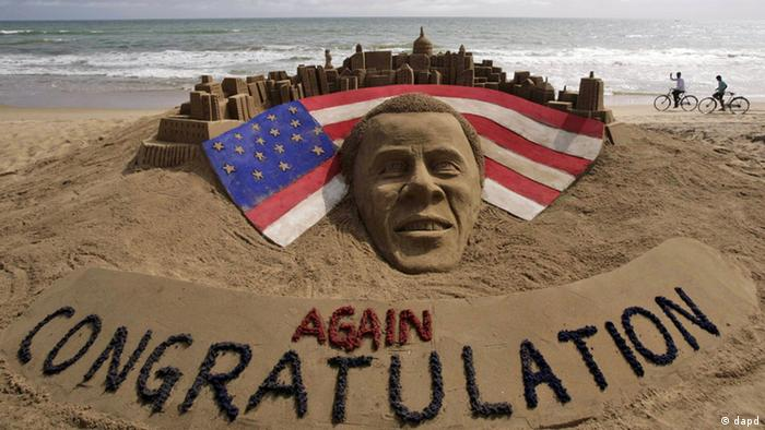 Cyclists ride on a beach passing by a sand sculpture congratulating U.S. president Barack Obama for a second term in office in Puri, India, Wednesday, Nov. 7, 2012. Obama captured a second White House term, blunting a mighty challenge by Republican Mitt Romney as Americans voted for a leader they knew over a wealthy businessman they did not. (Foto:Biswaranjan Rout/AP/dapd)