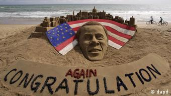 Cyclists ride on a beach passing by a sand sculpture congratulating US president Barack Obama (Photo: Biswaranjan Rout/AP/dapd)