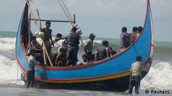 Members of Bangladesh Navy are seen with people rescued from a sunken boat in Bay of Bengal in Teknaf November 7, 2012. A boat carrying about 110 Bangladeshis and Rohingya Muslims from neighbouring Myanmar sank in the Bay of Bengal on Wednesday as they were heading to Malaysia