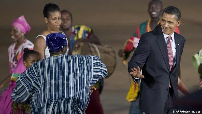 US President Barack Obama (R) smiles as he walks with First Lady Michelle Obama (2nd L) through a line of dancers during a departure ceremony in Accra, Ghana, July 11, 2009. AFP PHOTO/Jim WATSON (Photo credit should read JIM WATSON/AFP/Getty Images)
