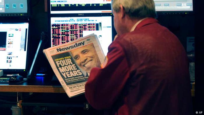A trader on the floor of the New York Stock Exchange looks at the front page of a newspaper the day after Pres. Barack Obama was re-elected, Wednesday, Nov. 7, 2012 in New York. With President Barack Obama elected to another term, U.S. investors dumped stocks Wednesday and turned their focus to a world of problems, including a fiscal cliff of tax increases and spending cuts at home and a deepening recession in Europe. (Foto:Henny Ray Abrams/AP/dapd)