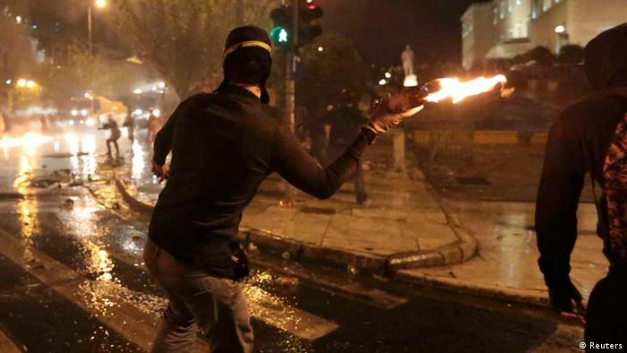 A protester throws a molotov cocktail at riot police during a 48-hour strike by the two major Greek workers unions in central Athens (Photo: REUTERS/Costas Baltas)