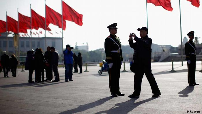 A man takes a picture next to a paramilitary police officer in front of the Great Hall of the People at Beijing's Tiananmen Square, November 7, 2012. Just days before the party's all-important congress opens, China's stability-obsessed rulers are taking no chances and have combed through a list all possible threats, avian or otherwise. Their list includes bus windows being screwed shut and handles for rear windows in taxis -- to stop subversive leaflets being scattered on the streets -- plus balloons and remote control model planes. The goal is to ensure an image of harmony as President Hu Jintao prepares to transfer power as party leader to anointed successor Vice President Xi Jinping at the congress, which starts on Thursday. REUTERS/Carlos Barria (CHINA - Tags: POLITICS ELECTIONS TPX IMAGES OF THE DAY)