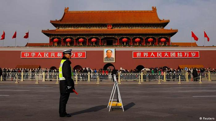 A policeman blocks the street in front of the giant portrait of former Chinese chairman Mao Zedong at Beijing's Tiananmen Gate November 7, 2012. Just days before the party's all-important congress opens, China's stability-obsessed rulers are taking no chances and have combed through a list all possible threats, avian or otherwise. Their list includes bus windows being screwed shut and handles for rear windows in taxis -- to stop subversive leaflets being scattered on the streets -- plus balloons and remote control model planes. The goal is to ensure an image of harmony as President Hu Jintao prepares to transfer power as party leader to anointed successor Vice President Xi Jinping at the congress, which starts on Thursday. REUTERS/Petar Kujundzic (CHINA - Tags: POLITICS)