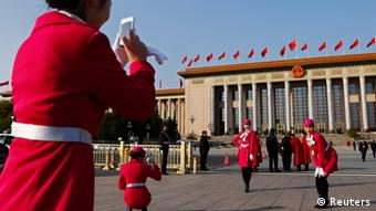 Hotel guides pose for a photo in front of the Great Hall of the People, the venue of the 18th National Congress of the Communist Party of China, in Beijing, November 8, 2012. REUTERS/David Gray (CHINA - Tags: POLITICS)