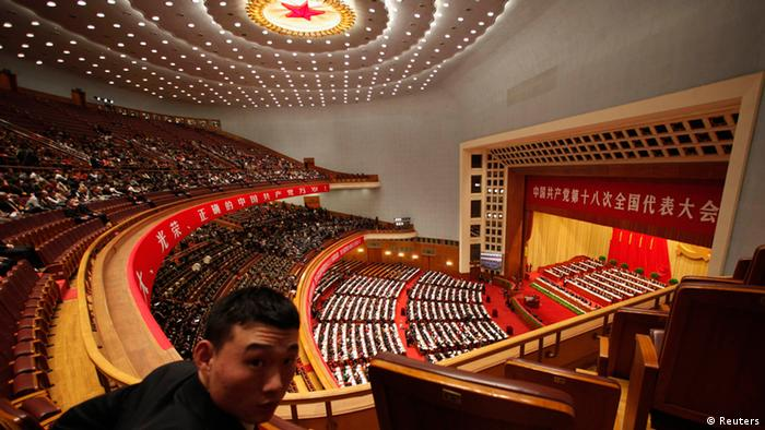 A security officer looks back as China's President Hu Jintao delivering a speech during the opening ceremony of 18th National Congress of the Communist Party of China at the Great Hall of the People in Beijing, November 8, 2012. REUTERS/Carlos Barria (CHINA - Tags: POLITICS)