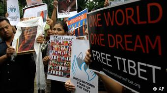 Tibetan exiles stand in silence with a portrait of their spiritual leader the Dalai Lama along with other posters seeking United Nations intervention on the alleged torture and cultural genocide on Tibetans inside Tibet, during a campaign in Kolkata, India, Monday, Sept. 3, 2012. According to London-based Free Tibet, 51 Tibetans have died of self-immolations protesting against the Chinese rule since 2009. (Foto:Bikas Das/AP/dapd).
