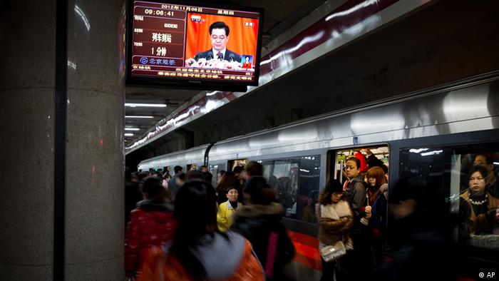 Commuters walk past a TV showing a live broadcasting of Chinese President Hu Jintao's remarks during the opening session of the 18th Communist Party Congress, at a subway station in Beijing, China, Thursday, Nov. 8, 2012. Preparing to hand over power after a decade in office, China's President Hu Jintao called Thursday for sterner measures to combat official corruption that has stoked public anger while urging the Communist Party to maintain firm political control. (Foto:Andy Wong/AP/dapd).