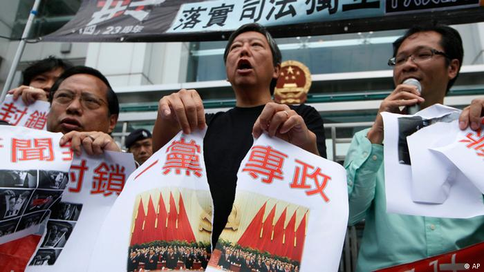 Pro-democracy activists tear a picture of the 18th Communist Party Congress held in Beijing with Chinese writing reading One party rule in China outside the Chinese central government's liaison office in Hong Kong Thursday, Nov. 8, 2012. Protesters demanded the Chinese government stop one party rule in China on the first day of a weeklong party congress in Beijing. (Foto:Kin Cheung/AP/dapd).