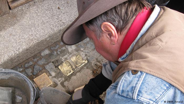 Gunter Demnig bei der Arbeit. Gerade schlägt er mit einer Spitzhacke ein Stück Asphalt aus dem Boden. Foto: Ronny Arnold