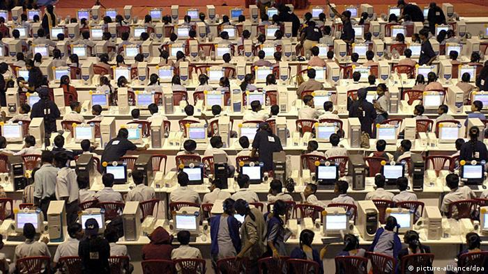 A large room with many Indian school students in Bangalore at computers