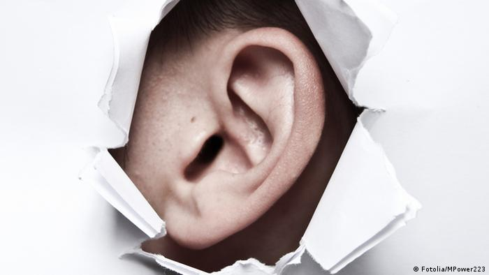 A symbolic image of an ear, seen through a hole in a piece of paper